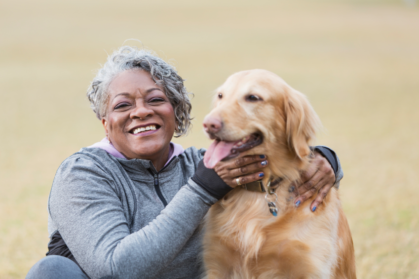 African American senior woman (60s) petting her golden retriever.  Focus on woman.